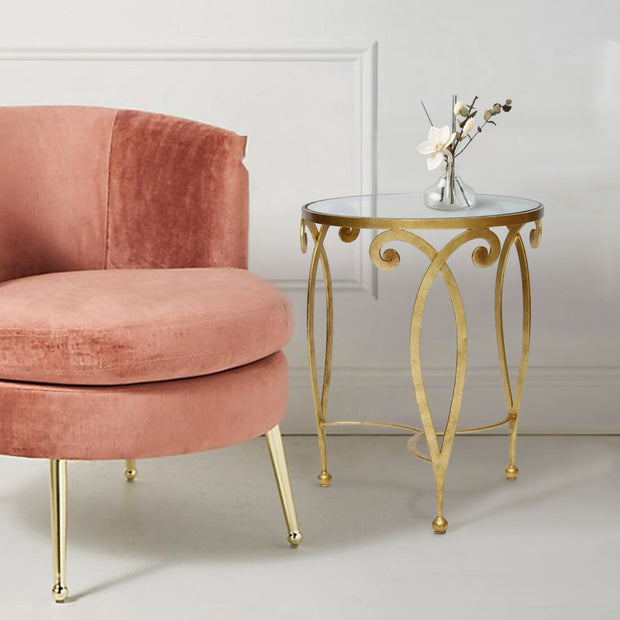 An exquisite golden end table made up of metal scrolls stands beside a pink arm chair