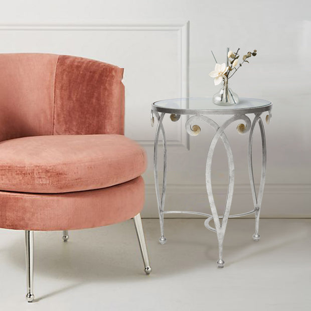 An exquisite silver end table made up of metal scrolls stands beside a pink arm chair