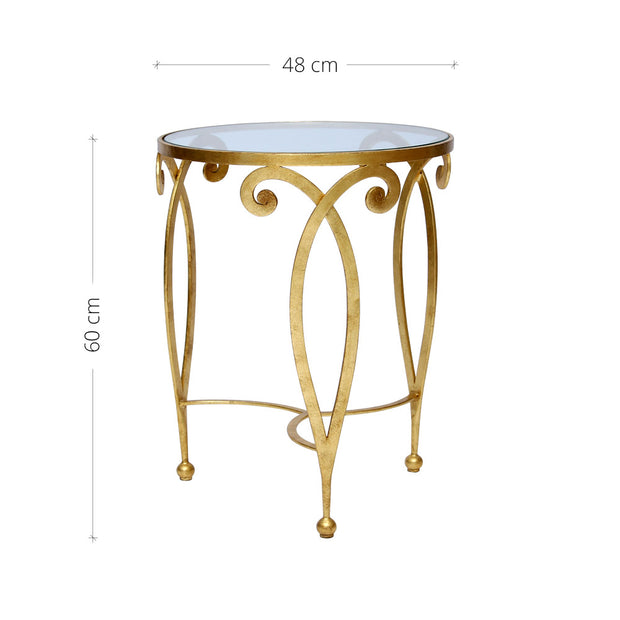 An exquisite golden end table made of metal scrolls topped with a clear round glass