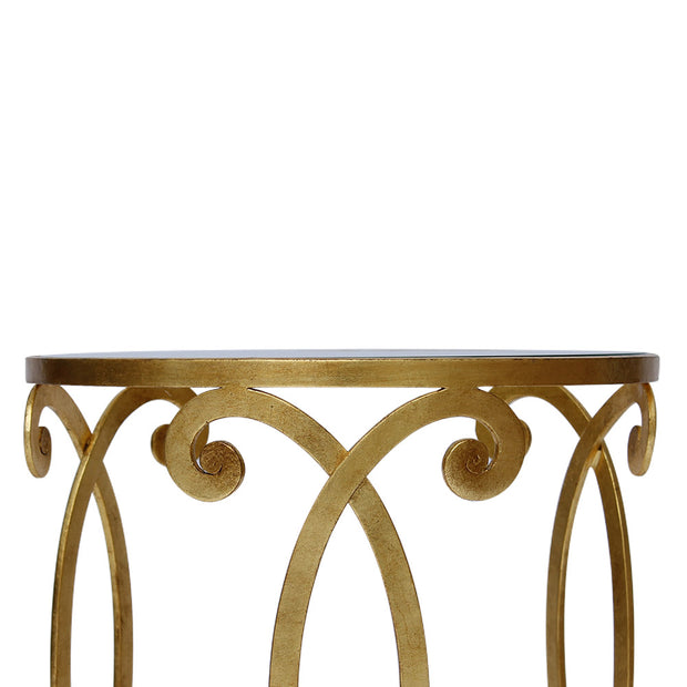 Detailed shot showing the scrolls  of a wrought iron side table with gold leaf finish