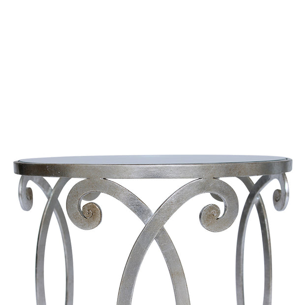 Detailed shot showing the scrolls  of a wrought iron side table with silver leaf finish