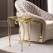 Elegant round side table with a gold leaf finish sits beside a contemporary arm chair