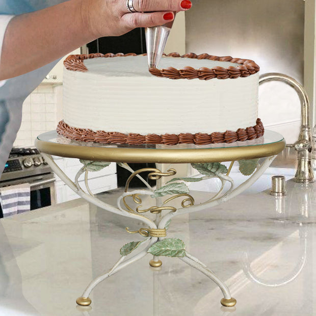 A lady decorates a cake sitting on an decorative stand over a kitchen counter
