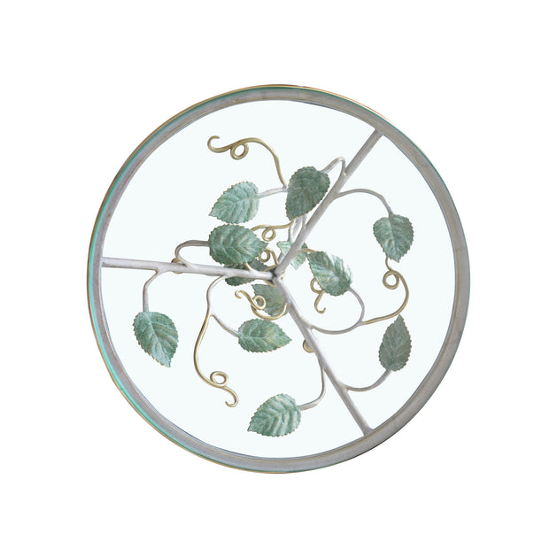 Top view of a round decorative cake plate inspired by leaves and branches; topped with a clear round glass