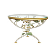 A decorative cake stand with a base adorned with leaves and branches inspired from nature topped with a round clear glass