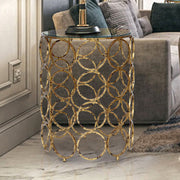 A trendy round side table made of forty golden rings with a clear glass top