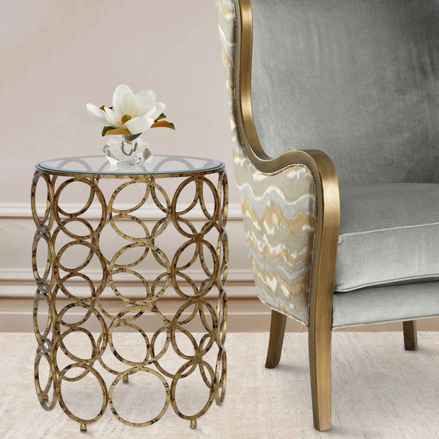 A unique accent table made of a collection of antique golden rings sits beside a classical blue arm chair