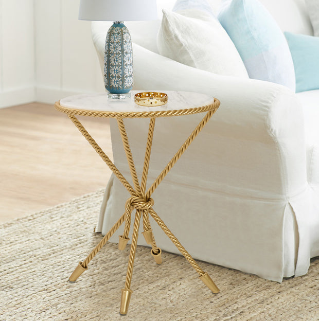 A golden round rope-themed side table with a white marble top stands beside a white sofa