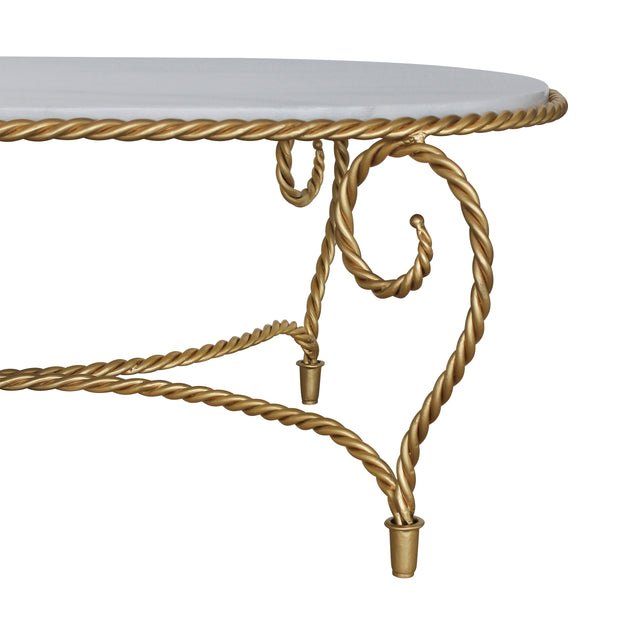 Detail of golden coffee table inspired by twisted rope, topped with natural marble