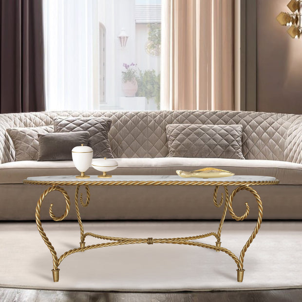 Cordelia oval-shaped coffee table inspired by twisted rope in Gold color and topped white natural marble in living room