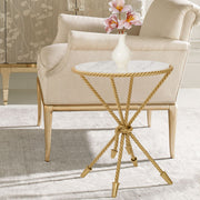 A unique golden accent table inspired by twisted rope sits beside a beige armchair