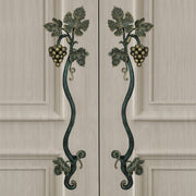 A pair of dark green and gold decorative pull handles inspired by grape vines mounted on closed wooden beige door