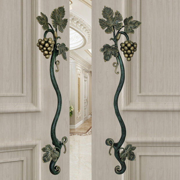 A pair of dark green and gold luxurious pull handles inspired by grape vines mounted on an open wooden beige door