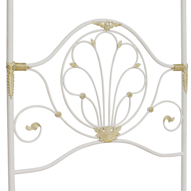 A wrought iron classical headboard for a single canopy bed, painted in a white and gold color
