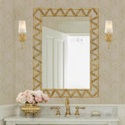 A rectangular golden mirror with a ribbon-like metal strip that forms a zigzag pattern along its perimeter; hangs above a wash basin
