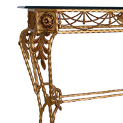 Close up of a classical wrought iron console comprised of twisted rope and classical motifs, painted in an antique golden finish, topped with clear glass
