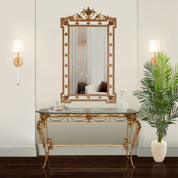 A classical wrought iron console table and mirror painted in an antique golden finish in a luxurious living space