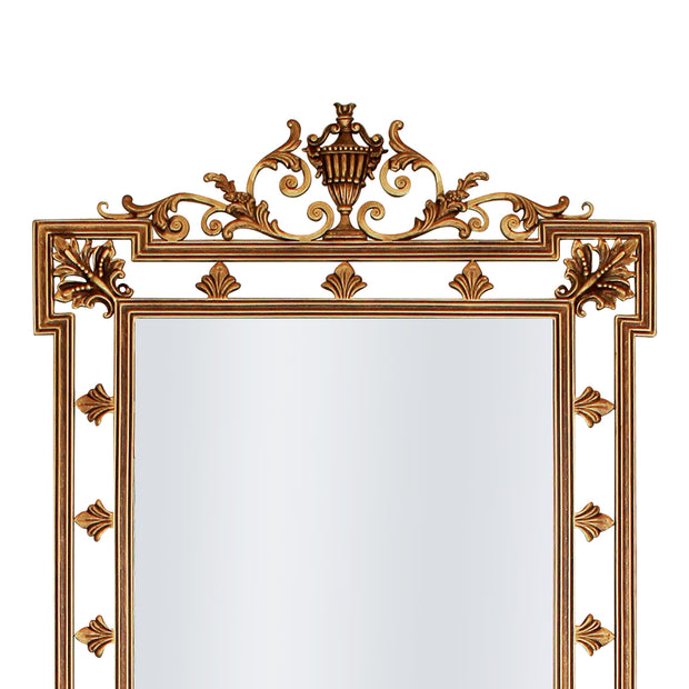 A close up of a rectangular hand forged mirror with classical motifs painted in an antique gold finish