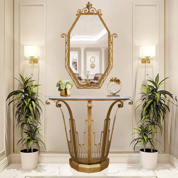 An Art Deco styled wrought iron console table and mirror painted in an antique golden finish in a luxurious living space