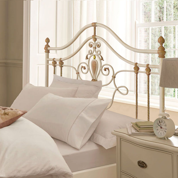 A girly wrought iron single bed with scrolls, leaves and motifs painted in white, pink and hints of gold