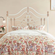 A girly wrought iron single bed with floral beddings