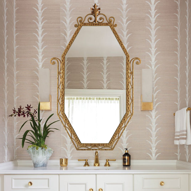 An Art Deco styled wrought iron mirror painted in an antique golden finish hangs above a stylish wash basin