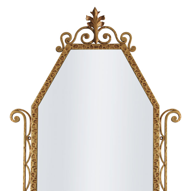 A close up of a classical hand forged mirror with textured scrolls painted in an antique gold finish