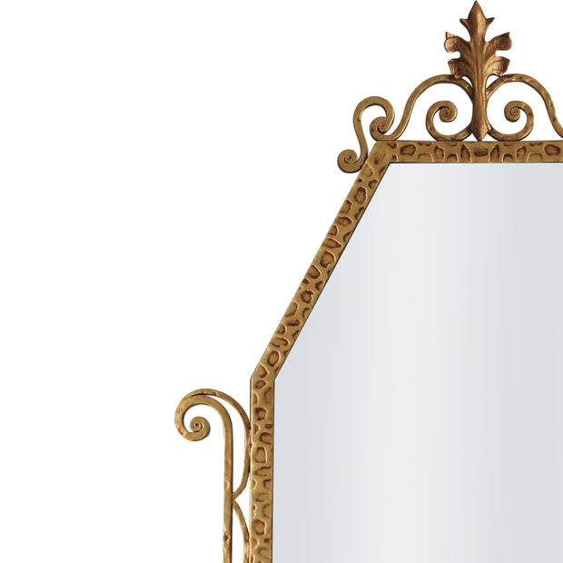 A close up of a classical hand forged mirror with textured scrolls painted in an antique golden finish