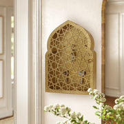 Key cabinet with a geometric pattern and Islamic arched top painted in an antique gold finish mounted on a wall