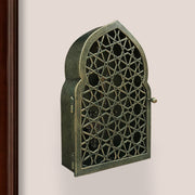 Key cabinet with a geometric pattern and Islamic arched top painted in an antique green-gold finish mounted on a wall beside a wooden door