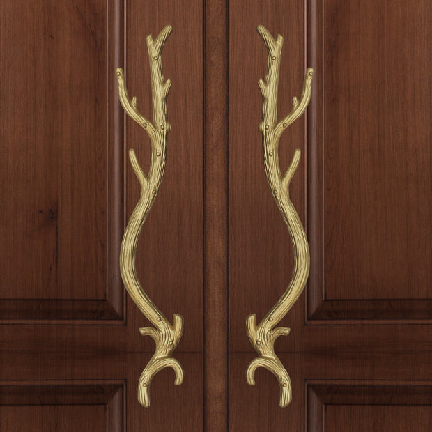 A pair of golden accent pull handles inspired by branches mounted on a closed wooden door