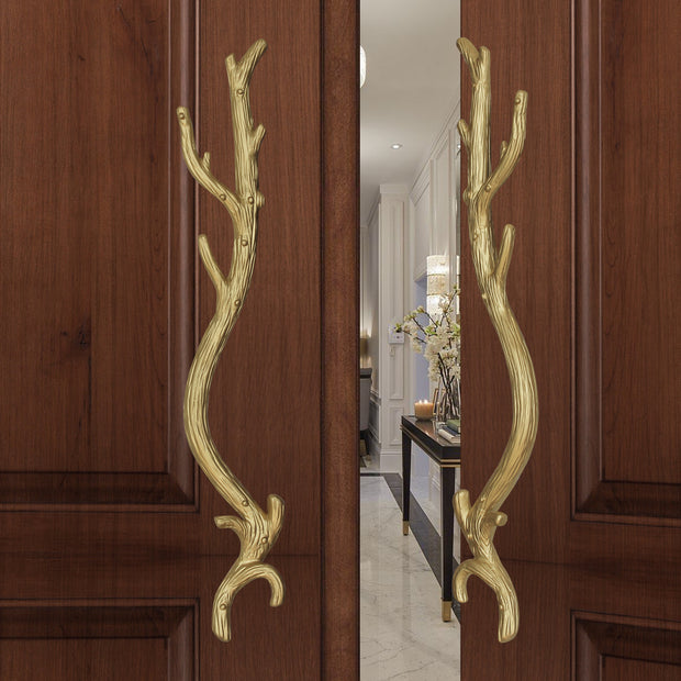 A pair of gold decorative pull handles inspired by branches mounted on an opened wooden door