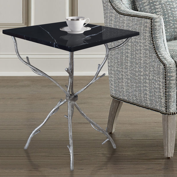 A unique side table with branch-like silver legs topped with a square piece of black marble, stands beside a blue armchair