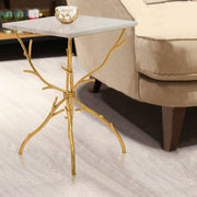 A unique side table with branch-like golden legs carry a square white piece of marble, stands beside an armchair