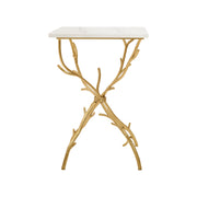 A trendy side table with golden legs that resemble branches topped with a white piece of marble