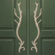 A pair of antique white accent pull handles inspired by branches mounted on a closed wooden door