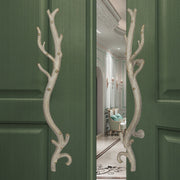 A pair of antique white decorative pull handles inspired by branches mounted on an opened wooden door