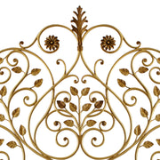 Close up of a wrought iron headboard made up of scrolls, leaves and flowers painted in an antique golden finish