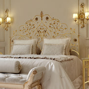 A luxurious wrought iron double bed inspired by nature; with branches, leaves and flowers painted in an antique gold finish