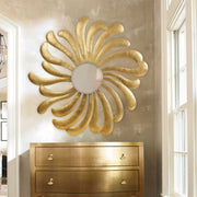 A unique golden round mirror with a design inspired by the sun hangs on the wall over a table