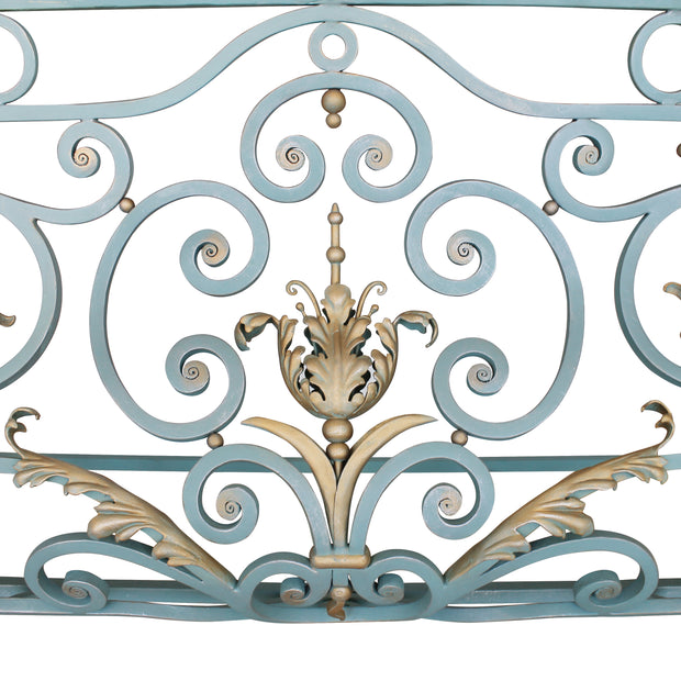 Close up of a classical console base made up of blue wrought iron scrolls and golden leaves