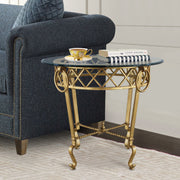 Classical style golden side table topped with clear glass stands beside a dark blue upholstered couch