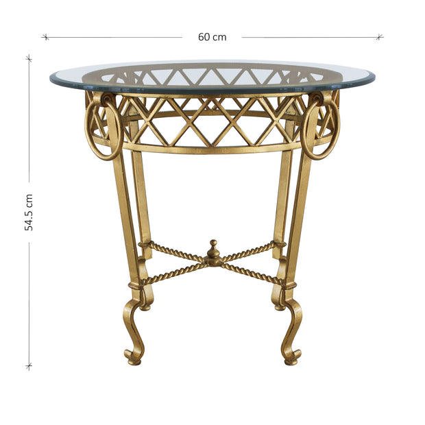A luxurious side table made of wrought iron in antique gold finish with a clear glass top