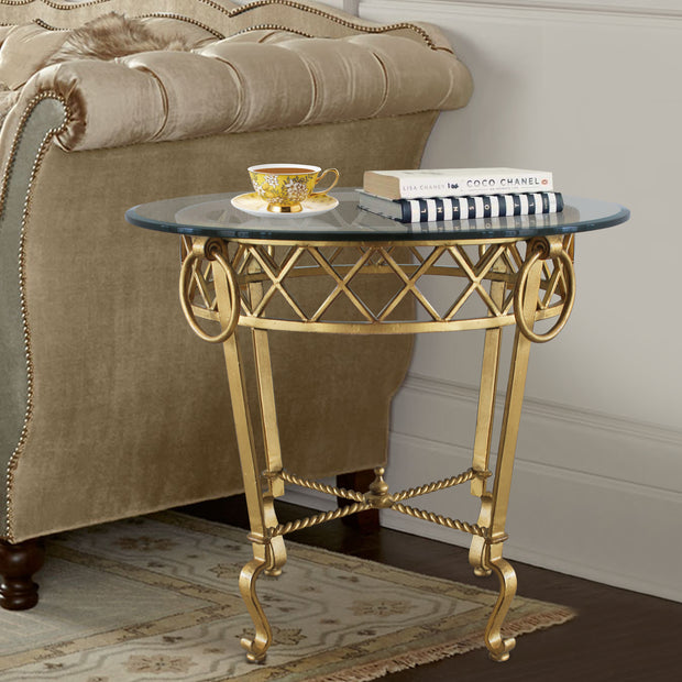 Classical style golden side table topped with clear glass stands beside a beige upholstered couch