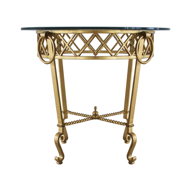 Frontal view of a classical wrought iron table painted in antique gold finish and topped with clear glass