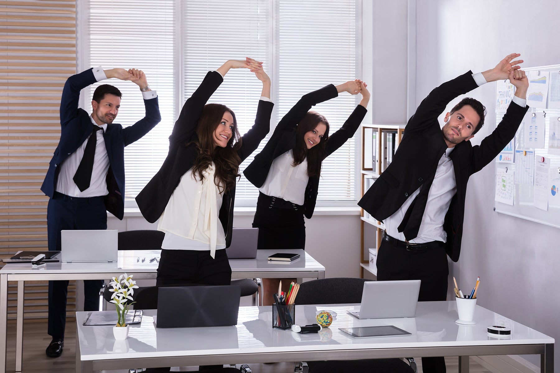 business people exercising behind desks