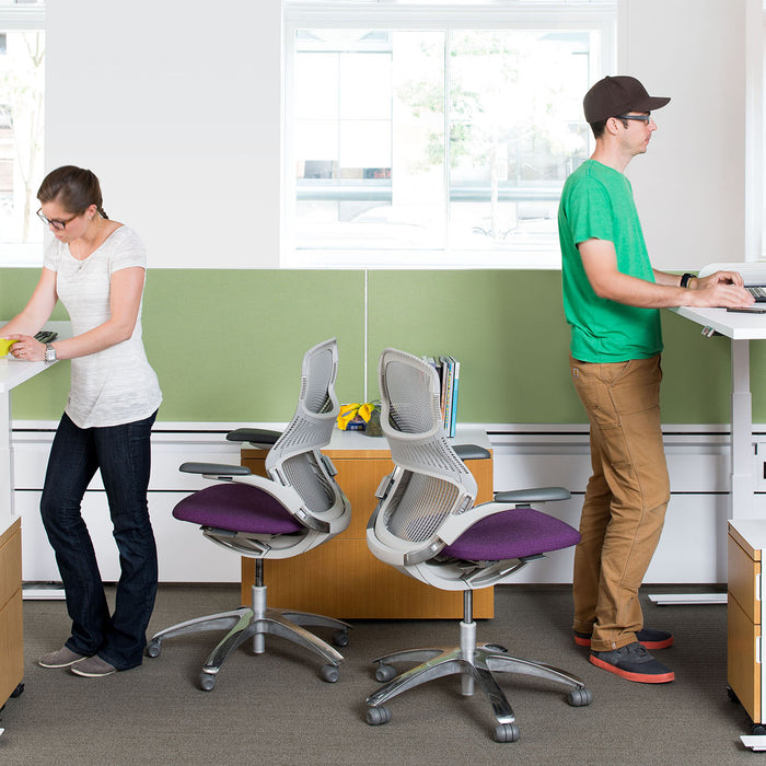 man and woman working at standing desks