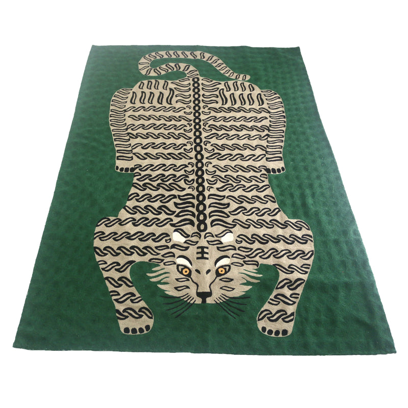 Bengal Tiger Carpet Emerald Green. Each carpet is made by hand by skilled artisans in Kashmir, the most northern part of India. They use a technique called chainstitch where colourful pure wool yarn is being stitched by a hook through thick cotton. Each carpet takes up to two months to complete.   We are stocking these beautiful carpets in a selection of bold colours in very small quantities. This one is a light beige and black tiger on a bold emerald green background.