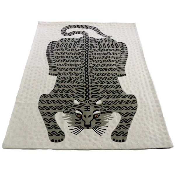 Bengal Tiger Carpet Ivory. Each carpet is made by hand by skilled artisans in Kashmir, the most northern part of India. Using a technique called chainstitch, colourful pure wool yarn is stitched by hook through cotton. Each carpet takes up to two months to complete.   We are stocking these beautiful carpets in a selection of bold colours in very small quantities. This special one is a grey tiger on an ivory background.
