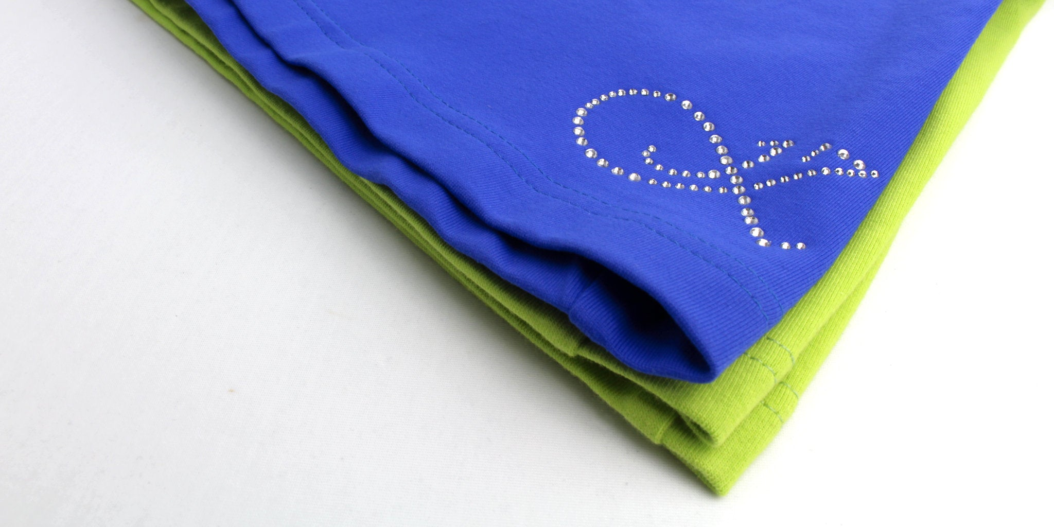 Pile of studio pole fitness clothing in green and blue colours made and designed in Brisbane Australia